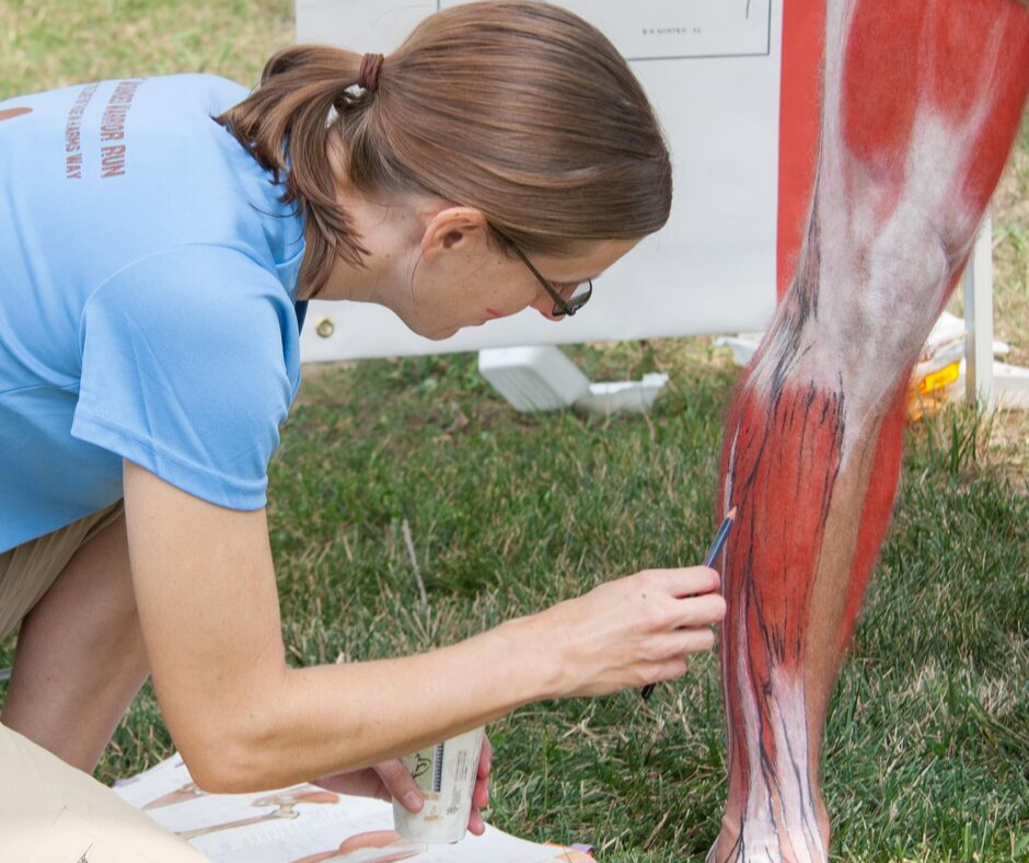 Elizabeth Weissbrod applying écorché painting on an athlete