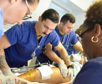 A group of people in medical scrubs work to transport a patient. Patient's leg is seen with wound dressings.