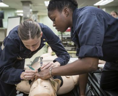 Two female Navy service members prepare simulated person for intubation.