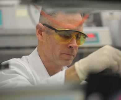 male scientist works with white gloves and protective eyewear.