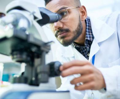 Middle Eastern Man in white lab coat looks into microscope
