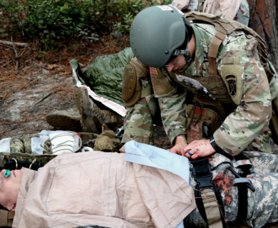 Soldier applying pressure to a wound to stop bleeding