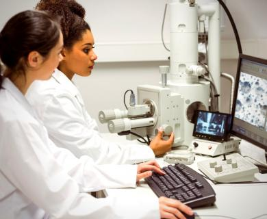 Two female scientists look at computer together while using microscope