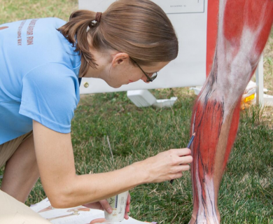 Elisabeth (Betsy) Weissbrod applying écorché painting on an athlete