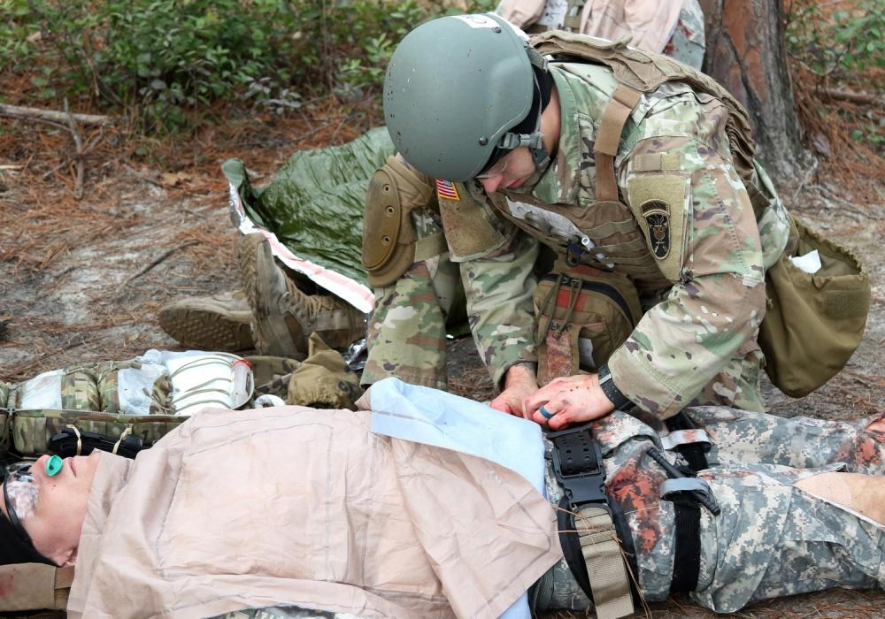 Army medic works on simulated patient to perform GSW triage