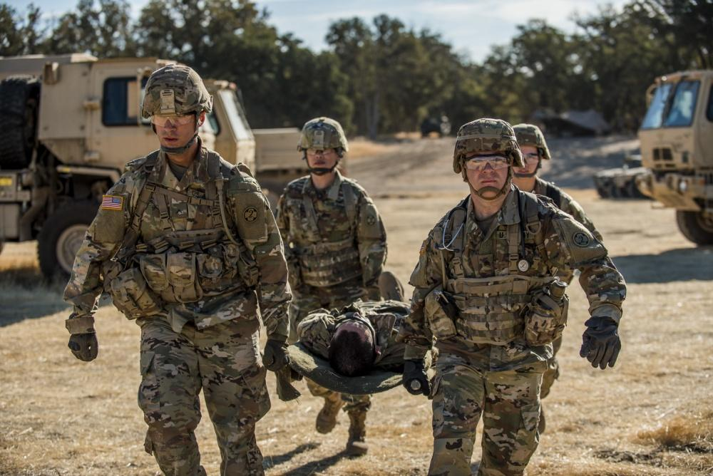 3 Army medics carry stretcher with simulated casualty. Vehicles are in the background.