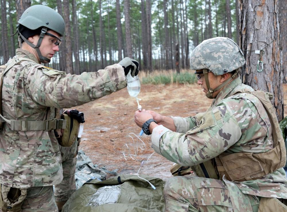 Two army medics work on a saline bag, outside in the forest.