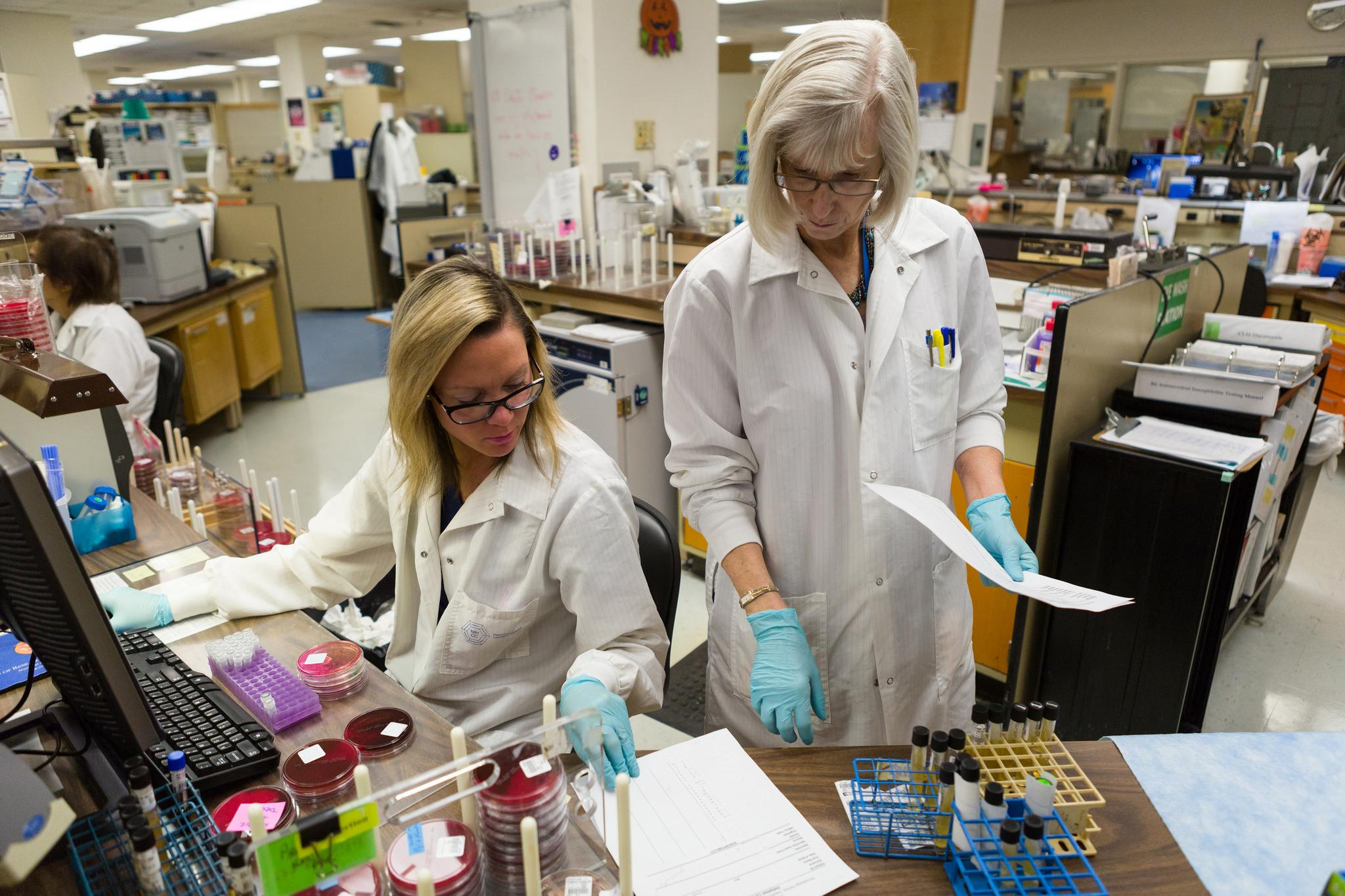 2 female scientists work in lab, one standing one sitting