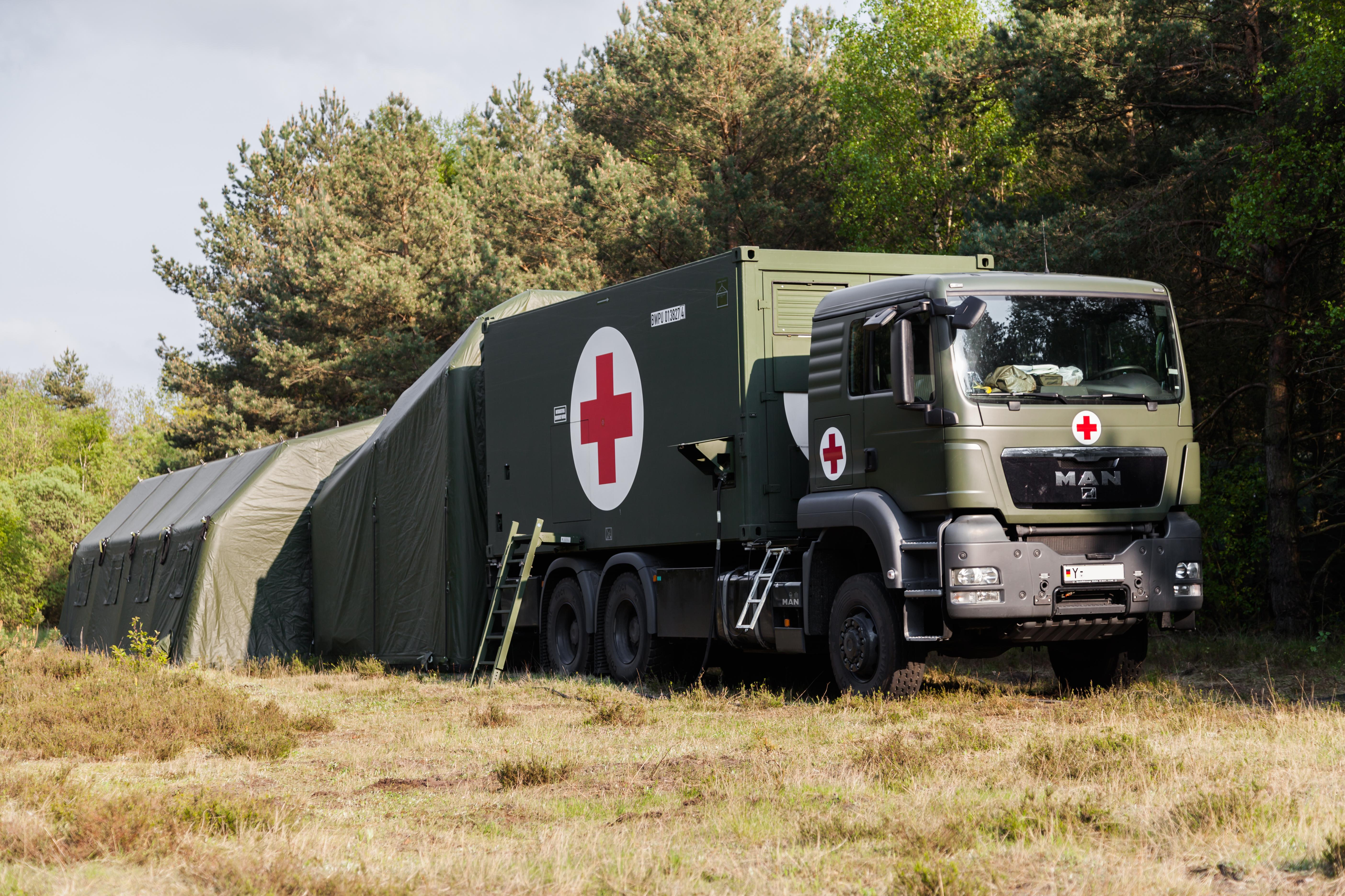 Medical transport vehicle with red cross on side