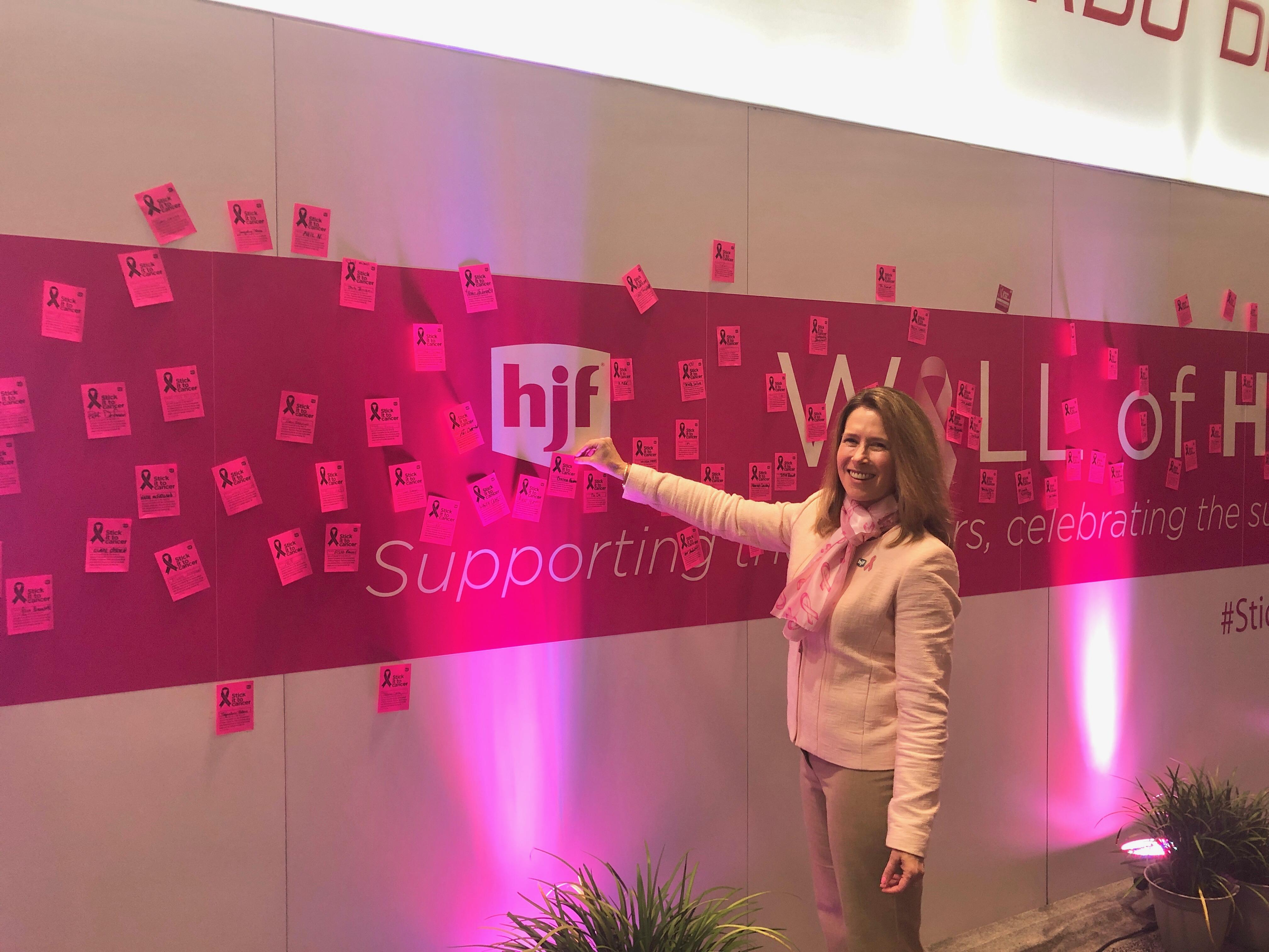 Woman posts sticky on pink wall of names